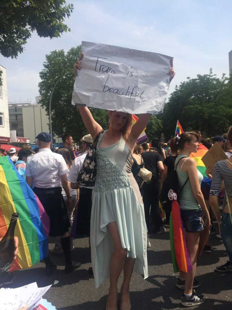 """Sophie in a Baal dress holding up a """"Trans is beautiful"""" banner at Berlin Pride"""